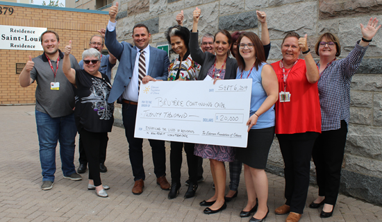 groupe of bruyere employees with thmbs up presenting cheque