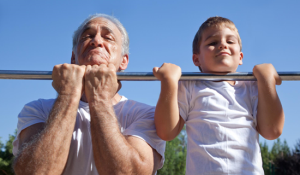 an senios man and young boy doing pull ups