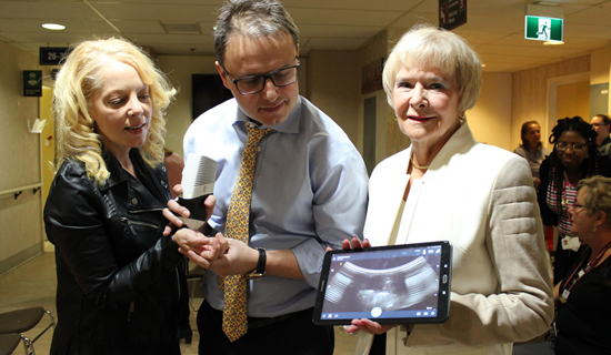 Peggy Taillon, Dr David Ponka and Claude Chapdelaine posing with a portable xray device and a tablet in their hands