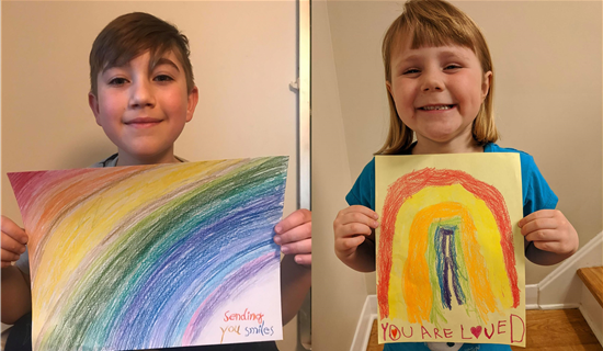 Little gir and girll holding rainbow drawings