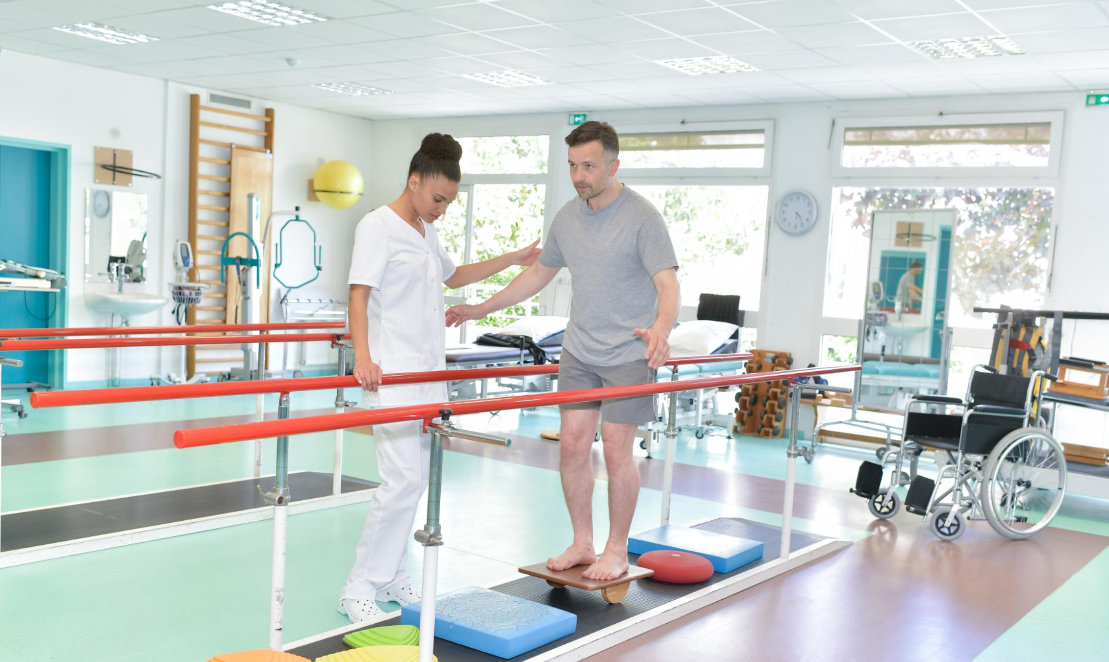 female physiotherapist assists male patient with balancing exercise