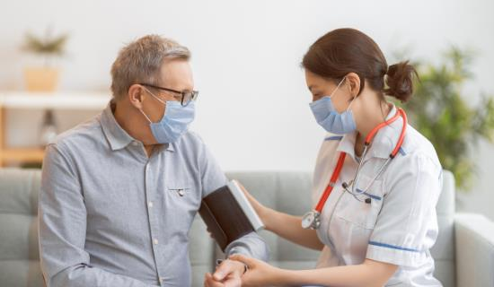 older man has blood pressure checked by female nurse