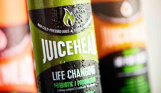 Close up of a plastic bottle filled with a green liquid and a logo that spell Juicehead
