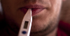 Close up of a man's mouth holding a thermometer