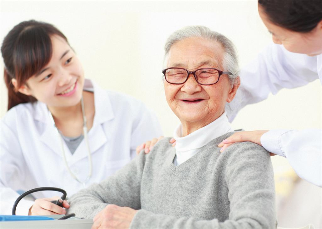 Elderly man smiling at his nurse