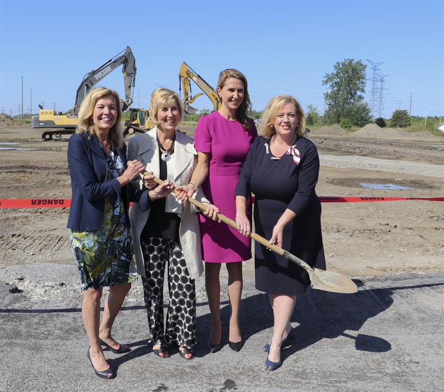 four woman posing in front of a construction site